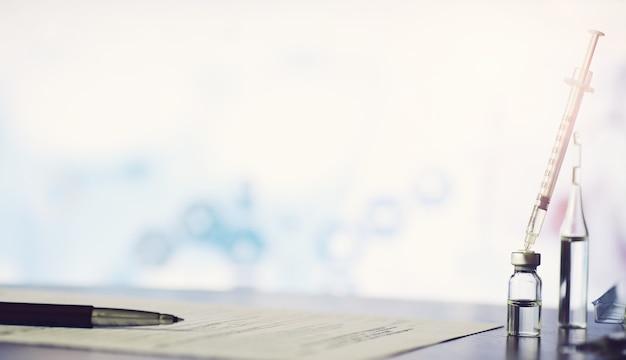 Un uomo firma un documento medico. attrezzature mediche sul tavolo. stetoscopio e fiale con siringhe. prende appunti in ufficio. centro medico.