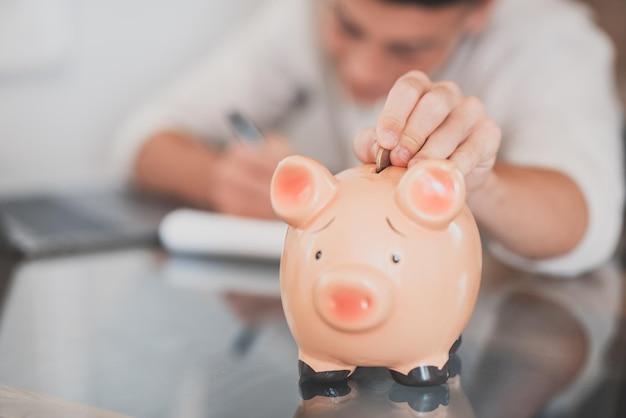 L'uomo si siede alla scrivania gestisce le spese, calcola le spese, paga le bollette online usa il laptop, fa l'analisi delle finanze domestiche, si concentra sul salvadanaio rosa. risparmia denaro per il futuro, sii previdente concetto