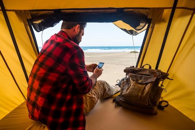 L'uomo si siede all'interno di una tenda in un campeggio libero selvaggio in spiaggia utilizzando un moderno telefono cellulare connesso per comunicare con i messaggi internet e lavorare come uno stile di vita di blogger nomade digitale
