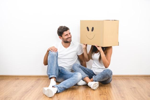 L'uomo si siede vicino alla donna con una scatola di cartone sulla testa