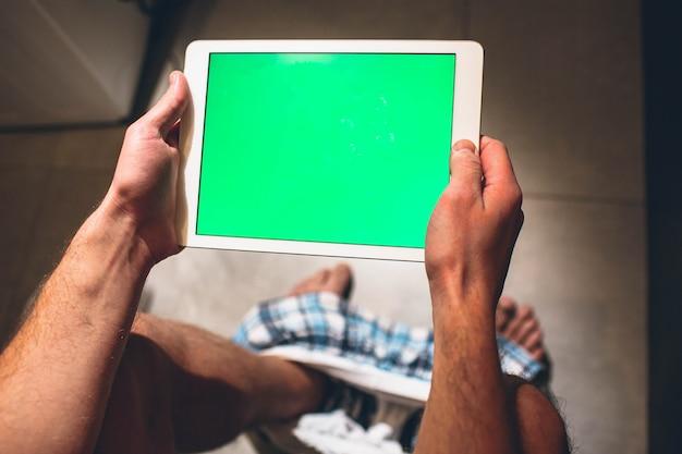 L'uomo si siede sulla pentola nella stanza di riposo e fa la defecazione. tieni il tablet in mano e gioca