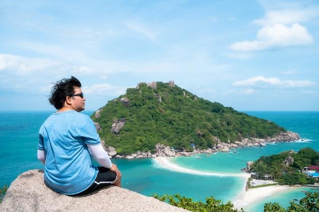 L'uomo si siede sulla roccia e guarda la vista al punto di vista dell'isola di nangyuan, luogo di destinazione turistica a suratthani, thailandia