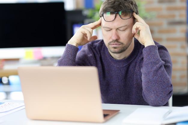 Ubicazione dell'uomo davanti al laptop e che tiene la sua testa. stanchezza al concetto di lavoro