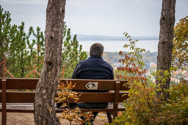 Un uomo si siede su una panchina presso la croce di luce (fenykereszt) vedetta in cima al monte csandor in vonyarcvashegy, ungheria
