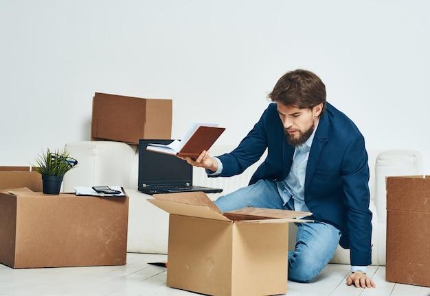 Un uomo siede scatole con cose che disimballano un nuovo lavoro professionale. foto di alta qualità