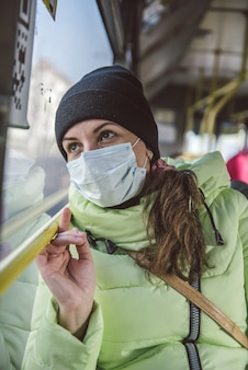 L'uomo si siede in un autobus cittadino in una maschera protettiva medica. protezione contro il coronavirus covid-19 nei trasporti pubblici.
