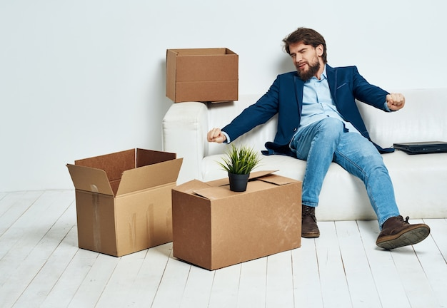 Un uomo si siede sul divano accanto alle scatole che disimballano una nuova posizione in movimento. foto di alta qualità