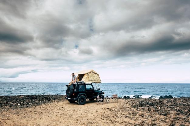 L'uomo si siede e riposa sul tetto della sua auto con la tenda