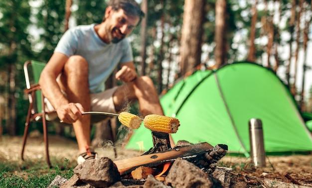 Un uomo si siede vicino a una tenda vicino a un falò e frigge il mais su uno spiedino in una pineta per il fine settimana. campeggio, ricreazione, escursionismo.