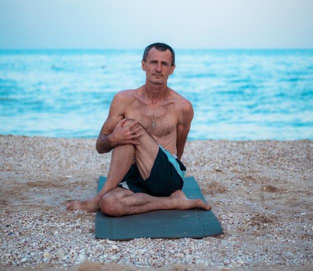 Un uomo si siede su un tappeto, si allunga e tiene la gamba con la mano e guarda avanti