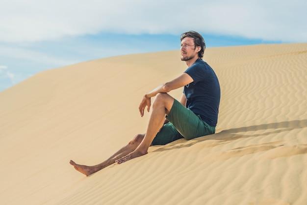 Un uomo si siede sulla sabbia nel deserto