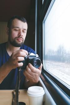 L'uomo si siede a un tavolo in un treno con una telecamera