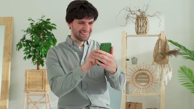L'uomo si siede a un tavolo, vince trionfante una lotteria online su un telefono cellulare, legge buone notizie inaspettate su uno smartphone