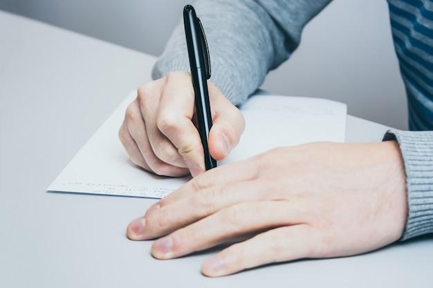 L'uomo si siede al tavolo e scrive con una penna su carta