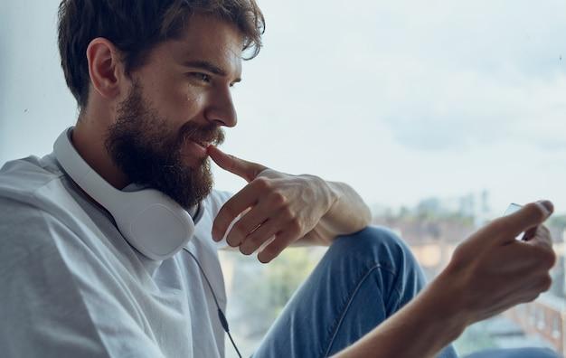Un uomo si siede su un davanzale con una comunicazione internet resto del telefono