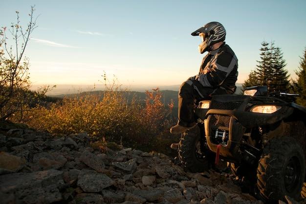 Uomo che si siede sul tramonto di sorveglianza del veicolo per qualsiasi terreno