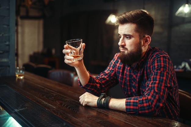 Uomo seduto al bancone del bar e bere alcolici
