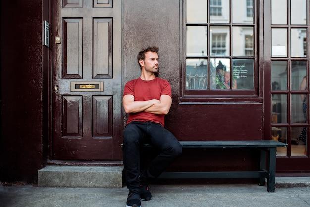 Equipaggi la seduta in un banco su un bello fondo marrone rossiccio