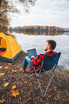 Uomo seduto su una sedia vicino al lago d'autunno che lavora al concetto di campeggio freelance per laptop