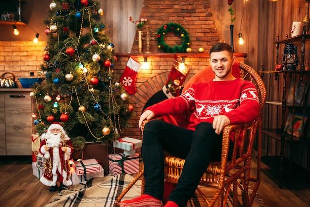Uomo seduto su una sedia vicino al camino, albero di natale con decorazioni, celebrazione delle vacanze di natale