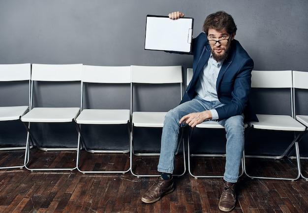 L'uomo seduto su una sedia in attesa di colloquio di lavoro riprende la formazione professionale.