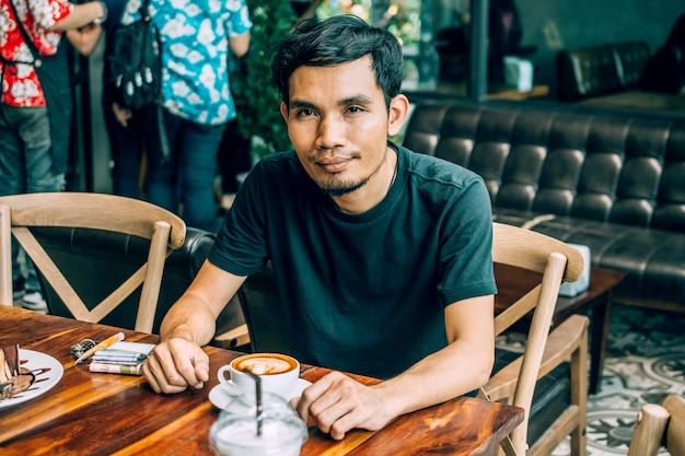 Equipaggi la seduta nella caffetteria per la bevanda nel tempo del caffè