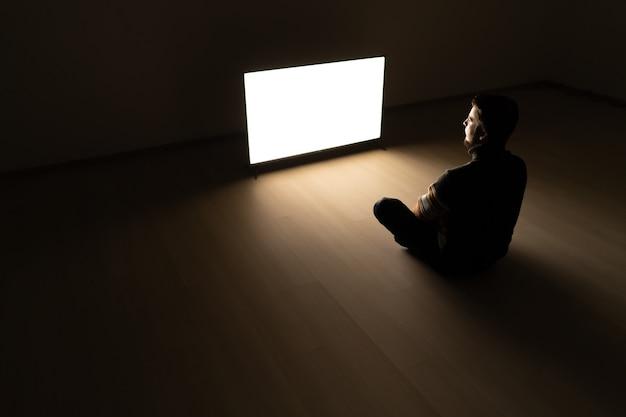 L'uomo seduto nella stanza buia davanti a un televisore