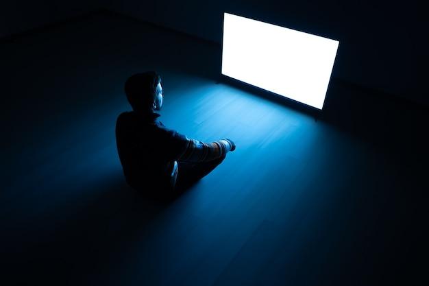 L'uomo seduto nella stanza buia davanti a uno schermo bianco