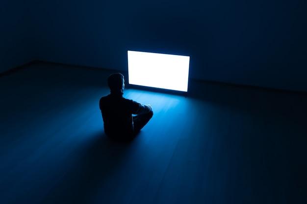 L'uomo seduto nella stanza buia davanti a un televisore bianco