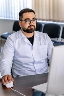 Uomo seduto alla scrivania. dottore in camice in ufficio vicino al computer. ufficio in ospedale.