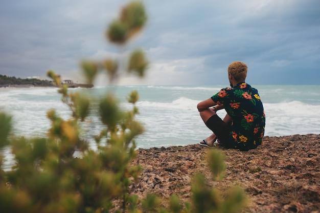 Uomo seduto sull'orlo dell'abisso di fronte al mare con grande