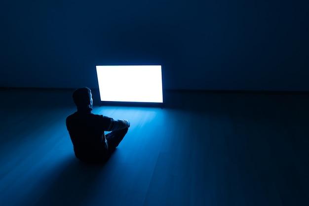 L'uomo seduto per terra davanti a uno schermo bianco