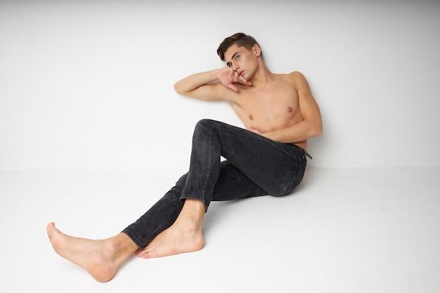 Uomo seduto sul pavimento torso nudo isolato