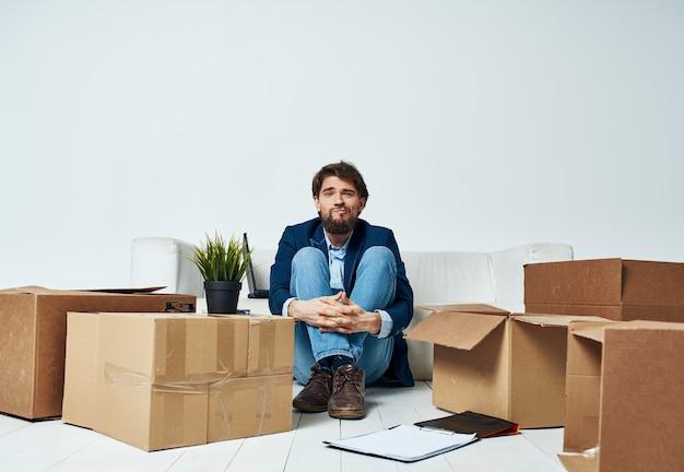 Uomo seduto sul pavimento con scatole di roba che si spostano in ufficio disimballaggio stile di vita. foto di alta qualità