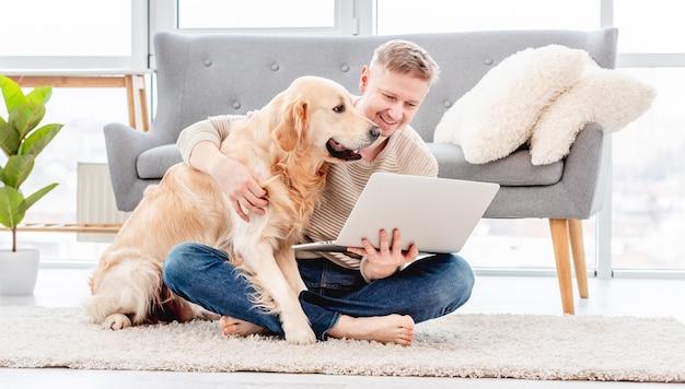 Uomo seduto sul pavimento con il computer portatile e che abbraccia il cane golden retriever nella stanza soleggiata. comunicazione online e lavoro a distanza