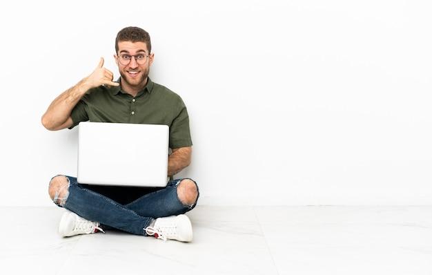 Uomo seduto sul pavimento con un laptop