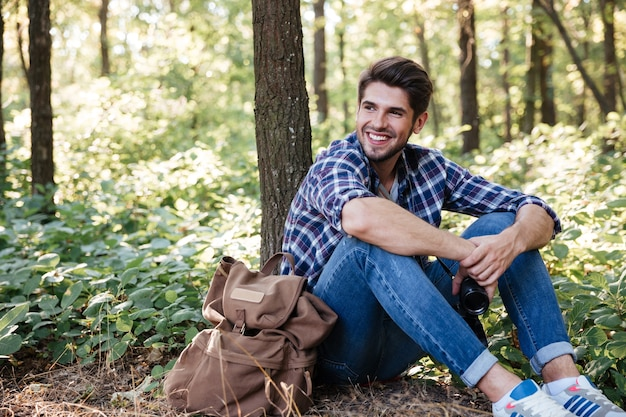 Uomo seduto nella foresta vicino allo zaino