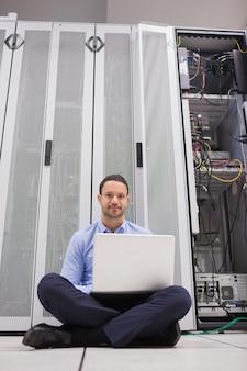 Uomo seduto di fronte a server con il suo laptop