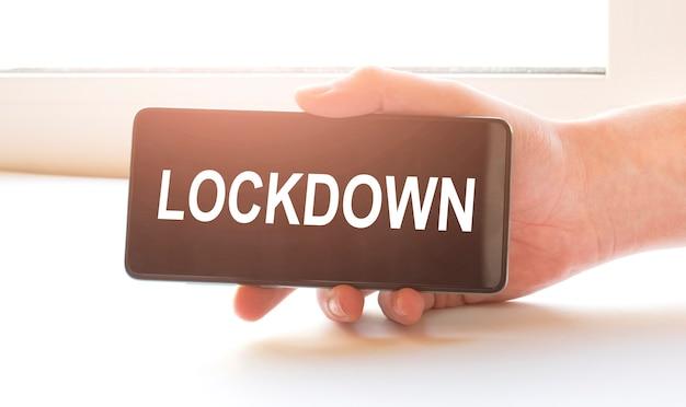 Uomo seduto a casa bloccato e tenendo il telefono nero con il segno blocco