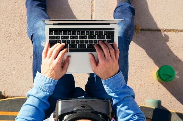 Uomo seduto su un longboard con laptop e occhiali vr nel parco, vista dall'alto