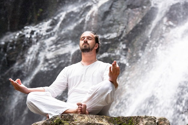 Uomo seduto nella posizione di yoga del loto sulla roccia sotto la cascata tropicale e la meditazione