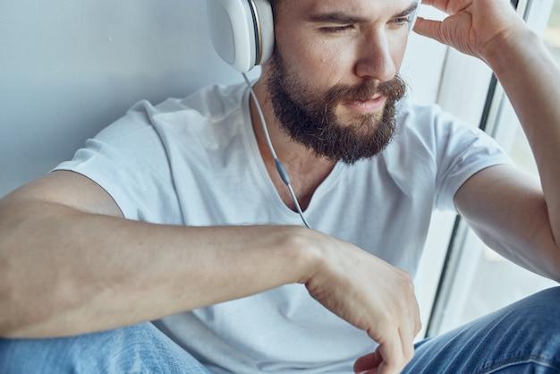 Uomo seduto vicino alla finestra con le cuffie che ascolta la musica con le cuffie
