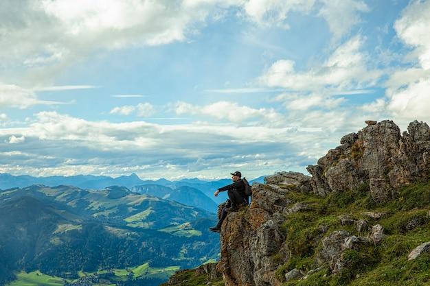 Un uomo seduto su una roccia alpi austriaveduta panoramica dall'alto