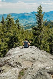 Uomo seduto su una roccia a guardare le montagne