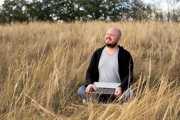 Uomo seduto e sorridente sull'erba con un computer portatile