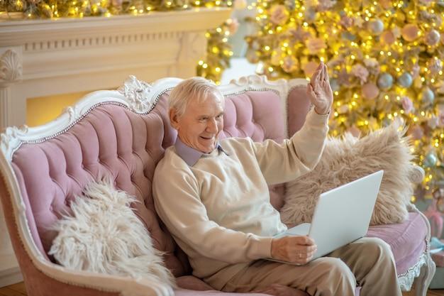 Uomo seduto sul divano e avendo una videochiamata