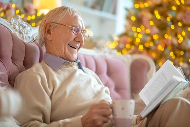 Uomo seduto su un divano a leggere un libro