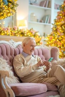 Uomo seduto su un divano utilizzando il telefono