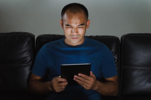 Equipaggi la seduta sul sofà, facendo uso del computer della compressa per lavoro o si rilassi a casa. lavorare da casa concetto.