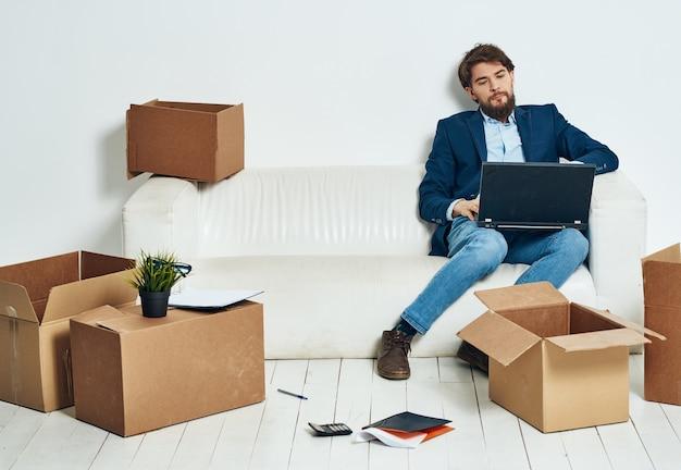 L'uomo seduto sul divano con laptop scatole per ufficio con le cose funzionano